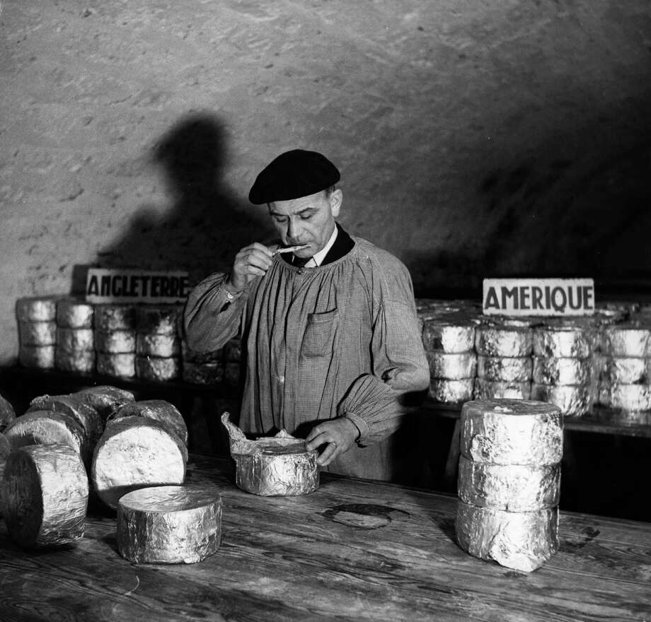 A taster tastes a sample of Roquefort cheese to determine its strength circa 1950. Behind him sit cheeses destined for America and England. Photo: Three Lions, Getty Images / Hulton Archive