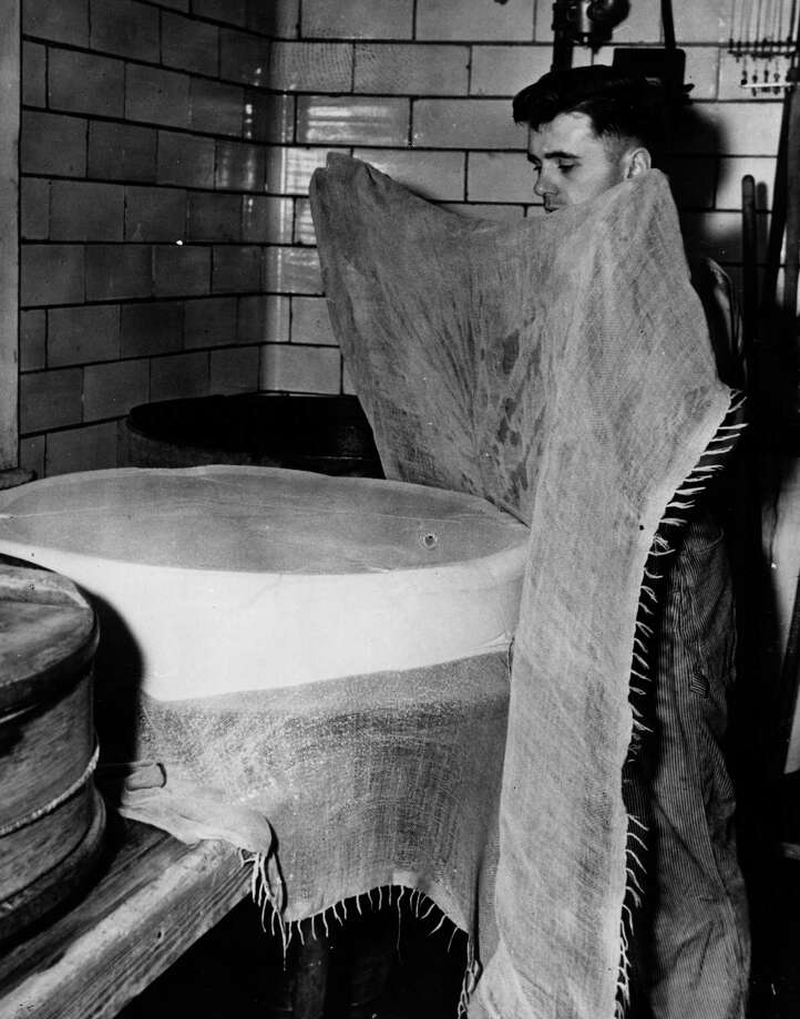 A cheese maker covers a newly formed cheese with a cloth circa 1955. Photo: Three Lions, Getty Images / Hulton Archive