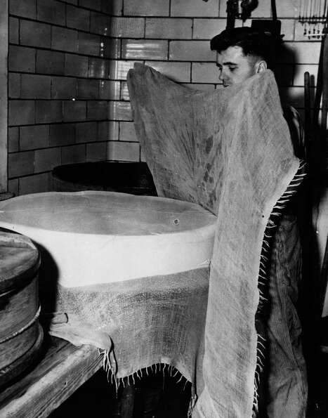 A cheese maker covers a newly formed cheese with a cloth circa 1955.