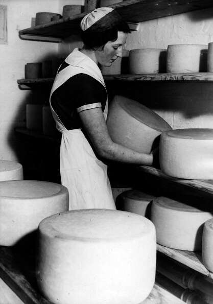 A student turns a large cheese on October 18, 1938  in the cheese maturing store at the Lancashire C