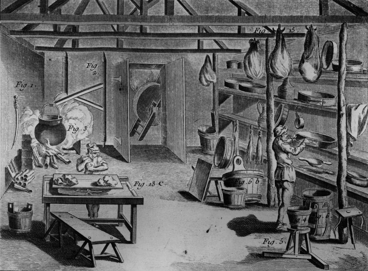A man makes Gruyere cheese in a dairy in this picture from 1768. The background shows cheeses hanging up to mature, a boiling cauldron and curds resting on shelves.