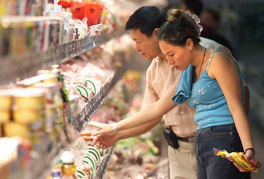 An Chinese couple spends several minutes looking at different imported soft cheeses at a grocery store on September 20, 2000 in downtown Beijing. Cheese is not a traditional Asian food, and Asians are largely lactose intolerant. Photo: STEPHEN SHAVER, AFP/Getty Images / AFP