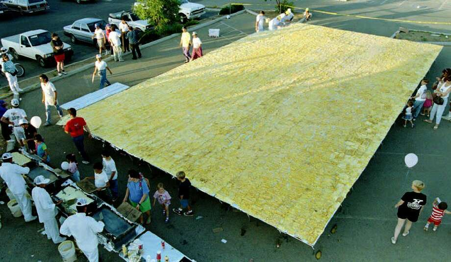 Participants in the effort to break the world's record for the largest omelette finish up a gigantic cheese omelette on June 15, 1993. The 17,000 egg omelette measured 1,364 square feet  and broke the previous world record set in Belgium in 1990. Photo: MIKE NELSON, AFP/Getty Images / AFP