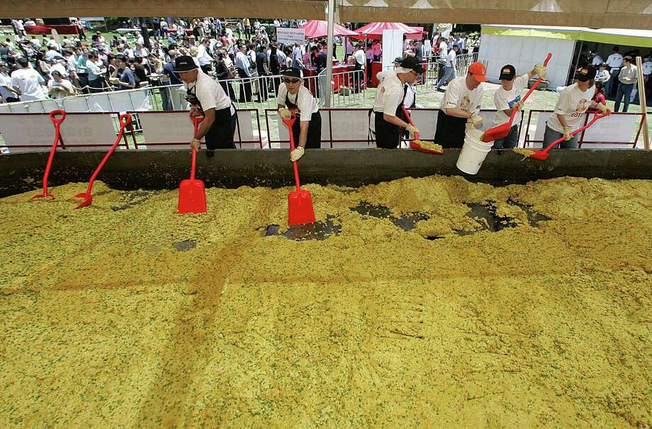 Volunteers shovel the world's largest risotto into buckets for serving to office workers on November 26, 2004, in Sydney, Australia. The record-breaking recipe called for 3,500 pounds of risotto rice, 1,750 pounds of peas, 700 pounds each of butter and Parmesan cheese and 20 gallons of olive oil. Photo: TORSTEN BLACKWOOD, AFP/Getty Images / 2004 AFP