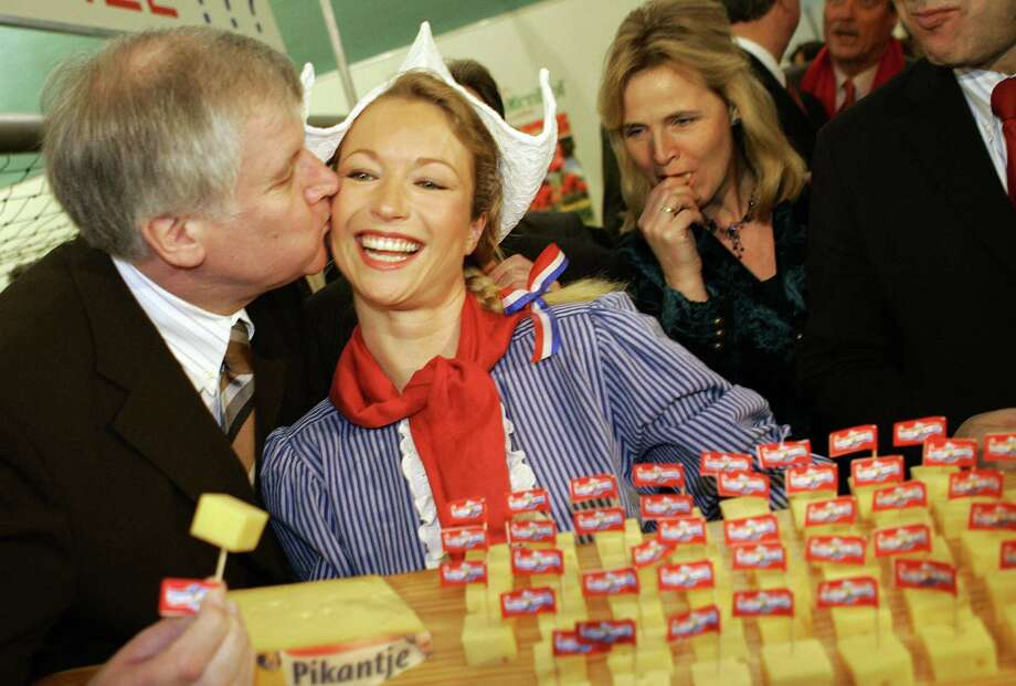 German Agriculture minister Horst Seehofer kisses a Dutch hostess posing with a plate of cheese on January 13, 2006, during a tour of the International Green Week (Gruene Woche) agricultural fair. Photo: MICHAEL KAPPELER, AFP/Getty Images / 2006 AFP