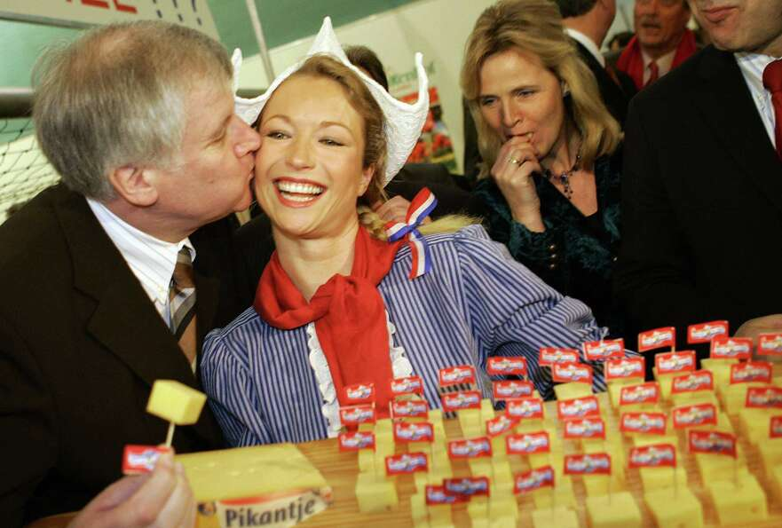 German Agriculture minister Horst Seehofer kisses a Dutch hostess posing with a plate of cheese on J