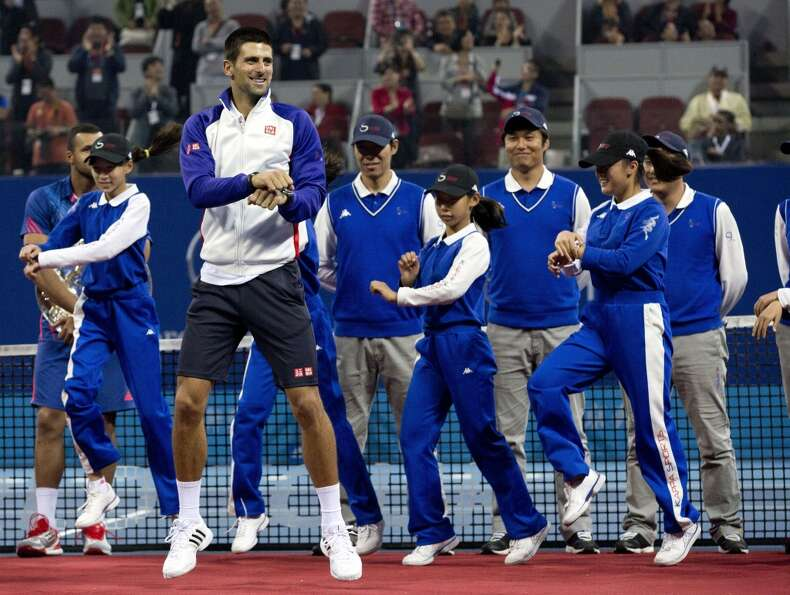 Serbia's Novak Djokovic, center, performs South Korean rapper PSY's  Gangnam Style dance with volunt