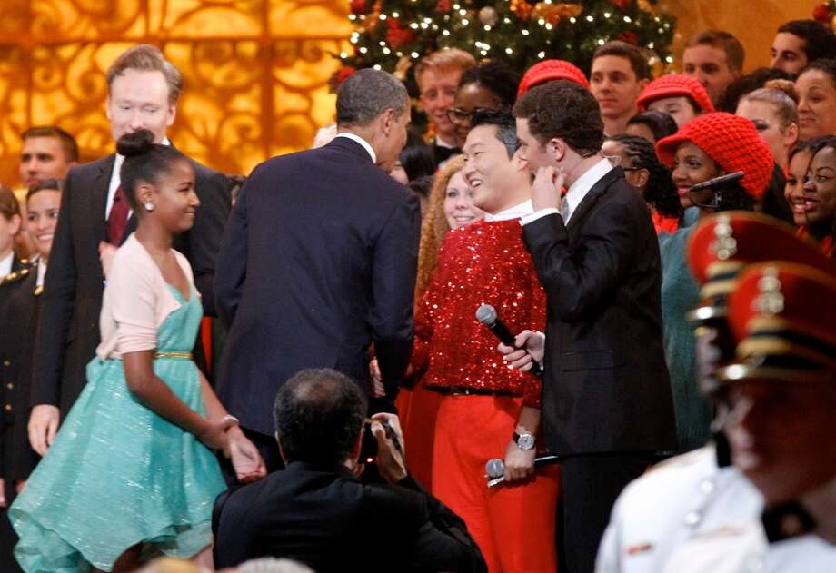 President Barack Obama shakes hands with South Korean musician PSY, center, next to host Conan O'Brien during the Christmas in Washington concert on December 9, 2012 in Washington, D.C. (Getty Images)