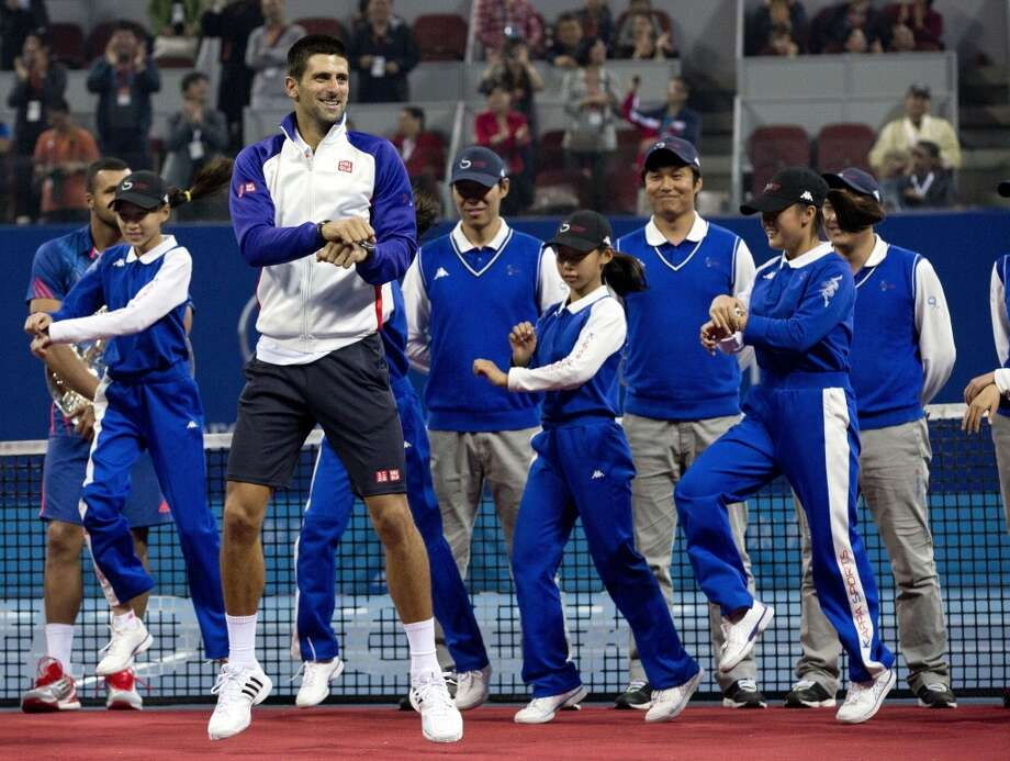 Serbia's Novak Djokovic, center, performs South Korean rapper PSY's  Gangnam Style dance with volunteers on a court after a prize presentation for the men's singles final match of the China Open tennis tournament in Beijing Sunday, Oct. 7, 2012.  (Associated Press)