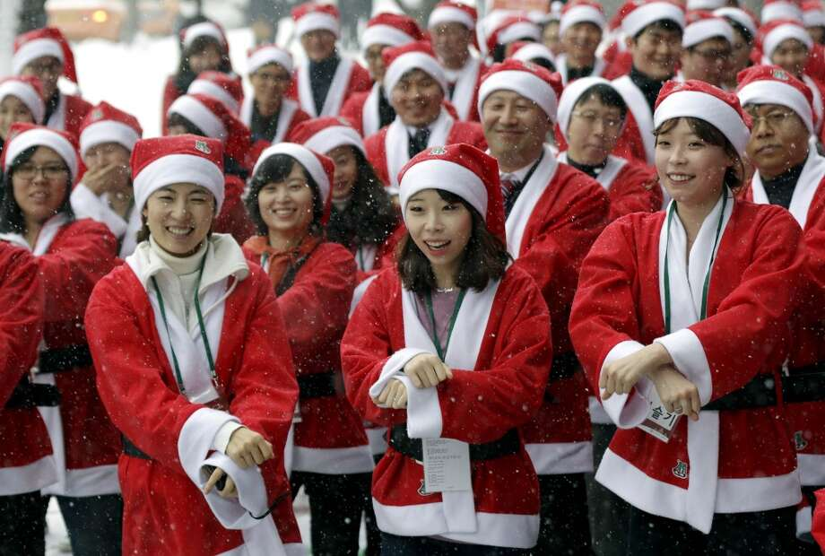 Volunteer workers, dressed in Santa Claus costumes, perform South Korean rapper PSY's Gangnam Style dance during an event to visit and give Christmas gifts to prematurely born babies in Seoul, South Korea, Wednesday, Dec. 5, 2012.  (Associated Press)