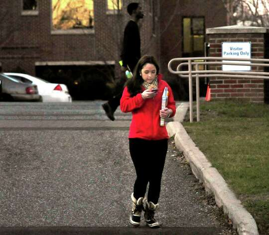 A woman is texting while crossing White Street in Danbury Thursday, Dec. 13, 2012. Photo: Michael Duffy / The News-Times