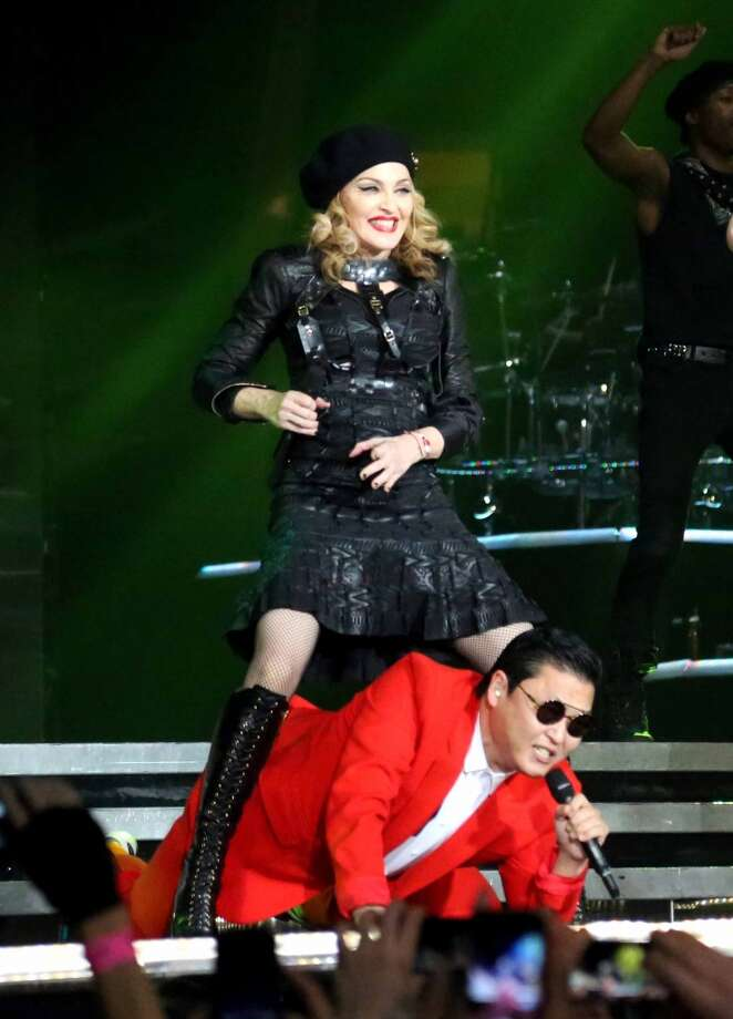 "In this Nov. 13, 2012 photo released by Guy Oseary, singer Madonna, left, performs onstage with South Korean rapper PSY during Madonna's MDNA concert at Madison Square Garden in New York. Psy joined the Madonna and her troupe of dancers onstage to perform his hit song ""Gangnam Style"".  (Associated Press)"