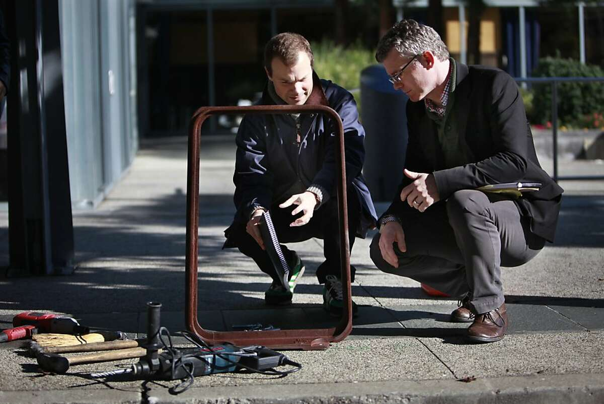 Calder Gillin (l to r), designer with CMG Landscape Architecture, which designed the bike racks, and Andrew Robinson, Director of Neighborhood Partnerships, Yerba Buena Community Benefit District, talk as they take a closer look at one during it's installation on Thursday, December 13, 2012 in San Francisco, Calif. The bike racks are made of recycled cast iron and sport a tire tread pattern.
