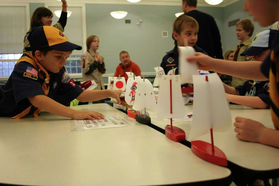 Cub Scout Nick Mathias, left, lines up the boat he built with the others preparing for the Raingutter Regatta held by Cub Scout Pack 192 on Saturday, Dec. 8, at Saugatuck Elementary School. Photo: Contributed Photo
