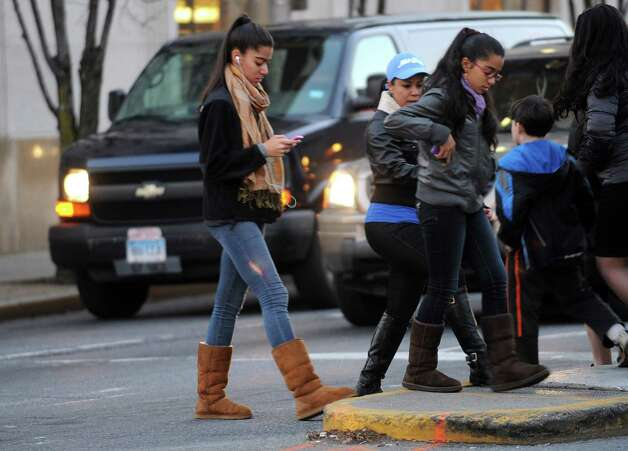 A pedestrian looks down at her smartphone while crossing Broad Street in Stamford on Thursday, December 13, 2012. Photo: Lindsay Niegelberg, Niegelberg / Stamford Advocate