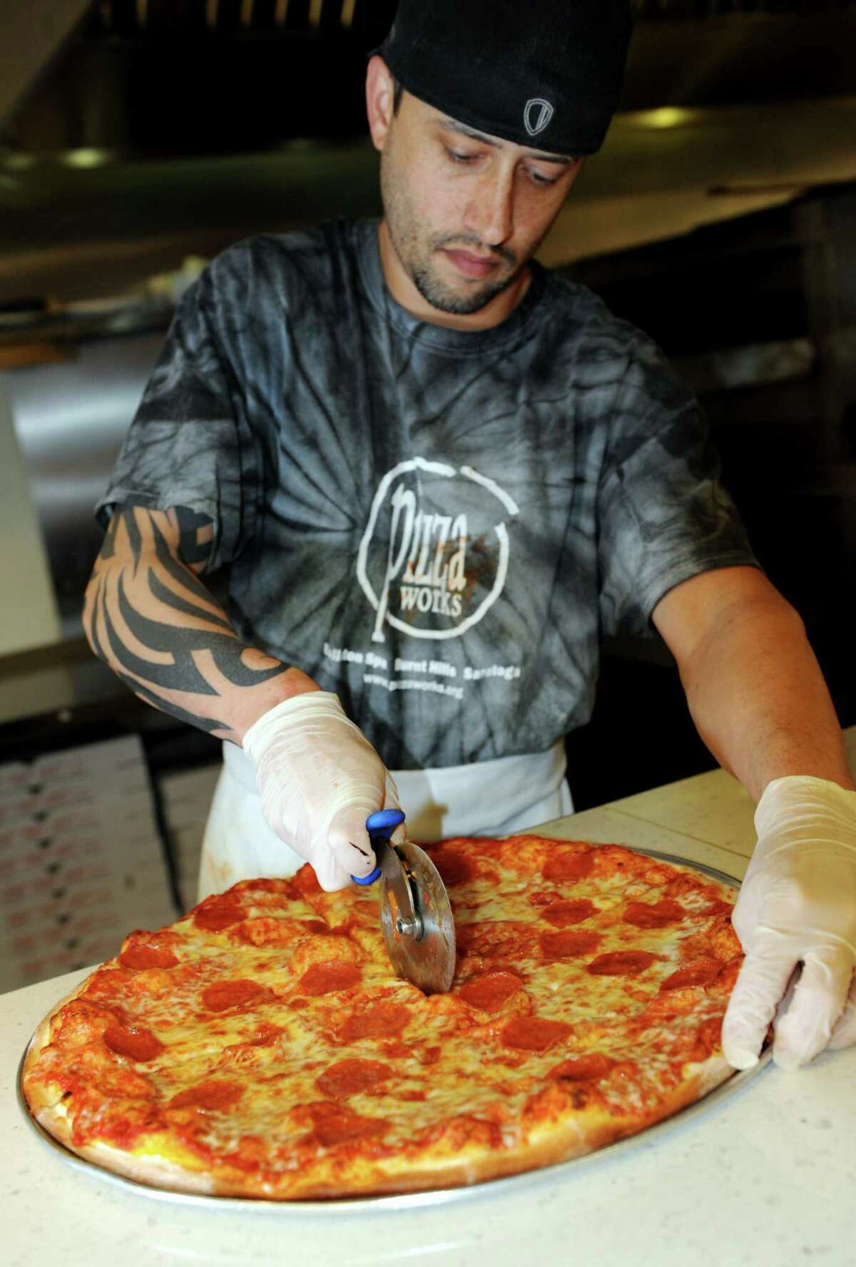 Manager Scott Provost cuts a pepperoni pizza on Tuesday, Dec. 11, 2012, at Pizza Works in Saratoga Springs, N.Y. (Cindy Schultz / Times Union)
