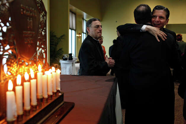 Archbishop Gustavo Garcia-Siller, right, embraces Charles Matt as Father Robert Ruhnke, left, looks on at the conclusion of the Catholics and Jews Celebrate Hanukkah event at the AT&T San Fernando Civic Centre in San Antonio on Thursday, Dec. 13, 2012. Photo: Lisa Krantz, San Antonio Express-News / © 2012 San Antonio Express-News