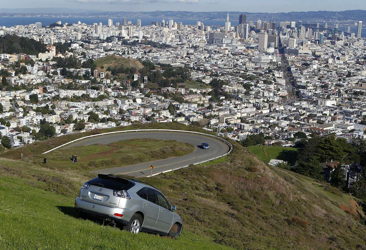 The driver of a Lexus SUV somehow lost control of his car and drove off the edge of the Twin Peaks lookout but managed to stop it about 50-feet down the hill in San Francisco, Calif. on Thursday, Dec. 13, 2012. A tow truck was called in to eventually remove the vehicle.