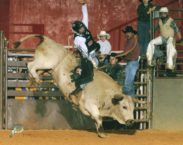 Robbie Teel, standing in the black hat, watches as his son, Cody Teel, rides in a competition earlier this year. Photo: Kami Teel