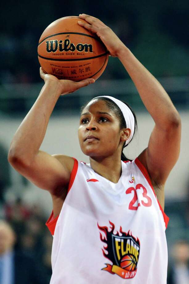 In this Nov. 24, 2012, photo, Shanxi Flame's Maya Moore shoots against the Jiangsu Dragons during a WCBA basketball game in Taiyuan, China. While her Minnesota Lynx team awaits the return of WNBA training camp in May, Moore is averaging 45 points a game and earning mid-six figures for the Flame, helping bring new fans to the women's game in a baseball crazed nation. (AP Photo/CHINATOPIX)  CHINA OUT Photo: Associated Press / CHINATOPIX