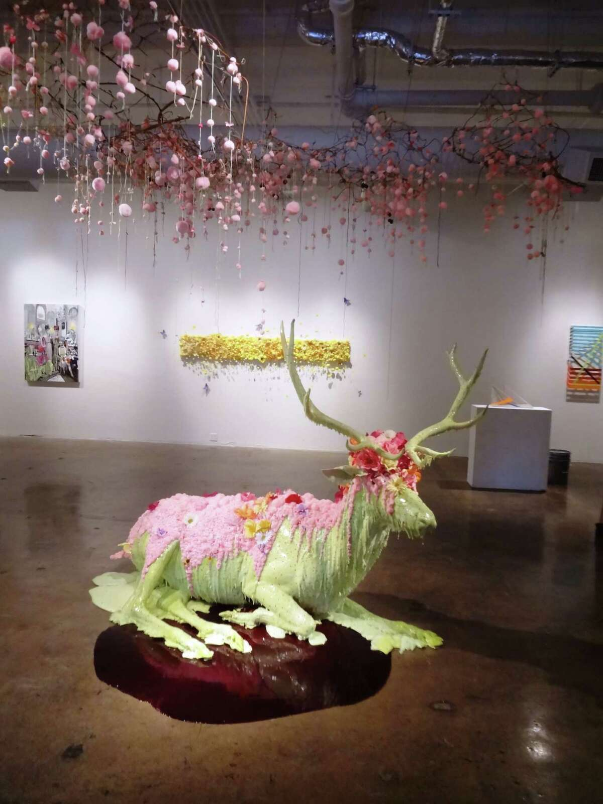 """Ann Wood strives for an """"attraction/repulsion"""" quality in large-scale sculptural installations such as """"Festoon,"""" which uses taxidermy forms, colorful foam, fake flowers and pink puff balls purchased at Hobby Lobby, the Houston artist's favorite store."""