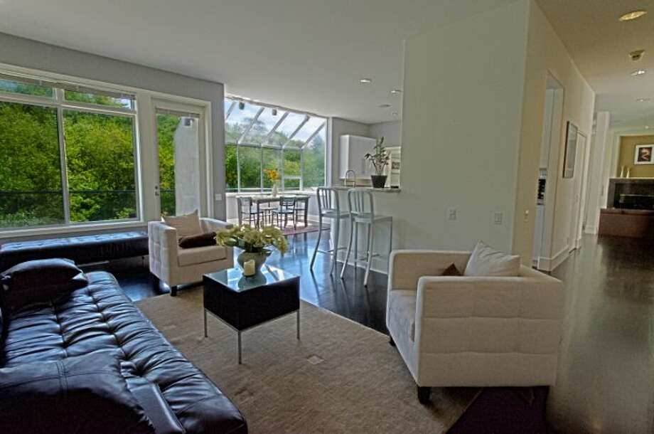 Living room of 1529 Magnolia Boulevard W. The 4,500-square-foot house, built in 1991, has four bedrooms and 3.5 bathrooms, a two-story entry, curved walls, big windows and four decks on an 8,160-square-foot lot. It's listed for $995,000. Photo: Courtesy Pat Craft/Windermere Real Estate