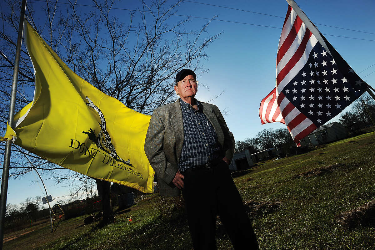 Michael Bishop poses Tuesday, Dec. 11, 2012, with a pair of flags flying in protest of the planned Keystone XL pipeline, near the entrance to his property south of Douglass, Texas, which is directly in the path of the project. Bishop scored an interim victory on Dec. 7, when Nacogdoches County Court at Law Judge Jack Sinz issued a temporary restraining order against parent company TransCanada Corporation in connection with Bishop's lawsuit, stopping work on the pipeline project pending a hearing scheduled for Thursday, Dec. 13, 2012. Bishop says that TransCanada lied to Texans when it said it would be using the Keystone XL pipeline to transport crude oil. (AP Photo/The Daily Sentinel, Andrew D. Brosig) MANDATORY CREDIT