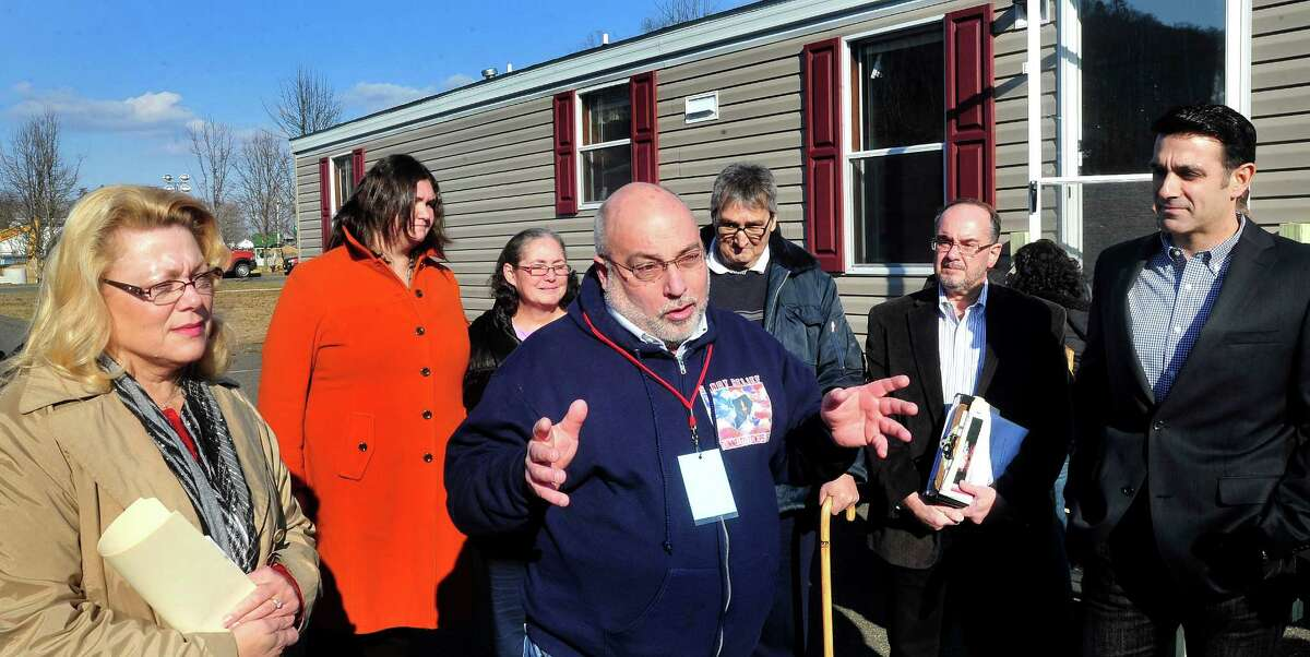 New Fairfield First Selectman John Hodge, center, speaks about temporary shelter for Hurricane Sandy victims from Staten Island, N.Y.,who stand behind him during a press confersence at Faith Church in New Milford Thursday, Dec. 13, 2012. Mobile homes are being brought to church property and utilities are being installed so families can move in later this month. New Milford Mayor Pat Murphy, left, and Faith Church Pastor Frank Santora, right, listen.
