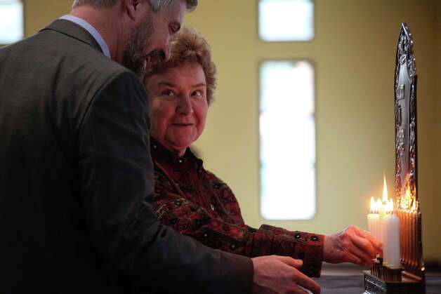 Sister Kathleen Coughlin and Joshua Sutin light a candle for the menorah together during the Catholics and Jews Celebrate Hanukkah event at the AT&T San Fernando Civic Centre in San Antonio on Thursday, Dec. 13, 2012. Photo: Lisa Krantz, San Antonio Express-News / © 2012 San Antonio Express-News