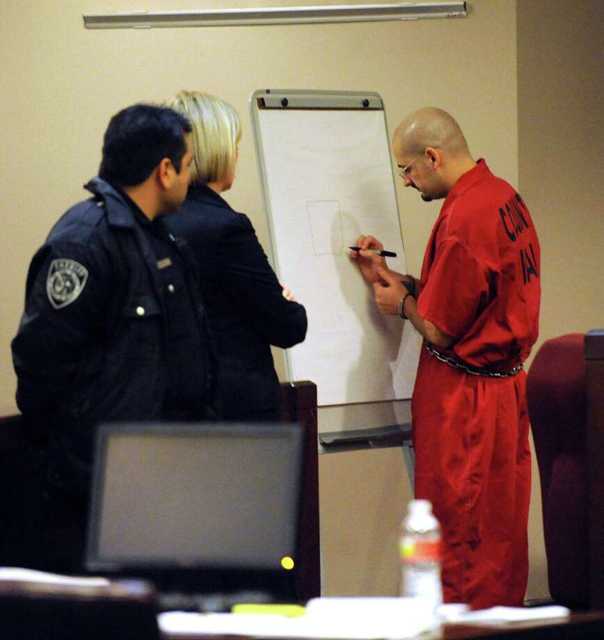 Death row inmate Juan Castillo diagrams a cell block during a hearing regarding fellow death row inmate Noah Espada and his request for a new trial before Judge Bert Richardson on Wednesday, Dec. 12, 2012. Photo: Billy Calzada, San Antonio Express-News / © 2012 San Antonio Express-News