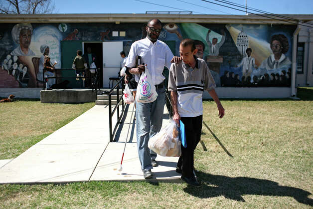 METRO - Michael Williams, left, holds onto Luis Valdez, right, as they leave the People's Church of Wheatley Courts' Sunday service to walk home to their Wheatley Courts apartments in San Antonio on Sunday, Feb. 24, 2008. Lisa Krantz/STAFF Photo: LISA KRANTZ, SAN ANTONIO EXPRESS-NEWS / SAN ANTONIO EXPRESS-NEWS