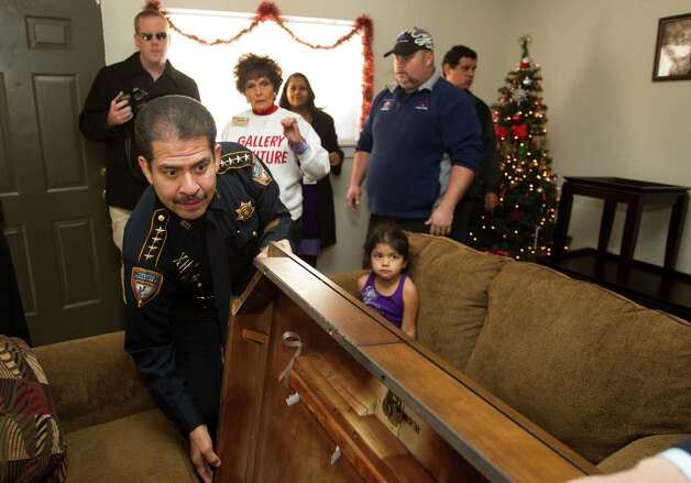 "Sheriff Adrian Garcia helps deliver new furniture to Patricia Mejia and her children Thursday, Dec. 13, 2012, in Houston. The Harris County Sheriff's Department and Gallery Furniture partnered to surprise Mejia, a single mother of seven, by furnishing her two-bedroom apartment with living room furniture, new beds and a kitchen table. ""Now that I have my own bed, I feel like a queen,"" said sixth grader Genesis Montano, after years of sleeping with her siblings. Photo: Brett Coomer, Houston Chronicle / © 2012 Houston Chronicle"