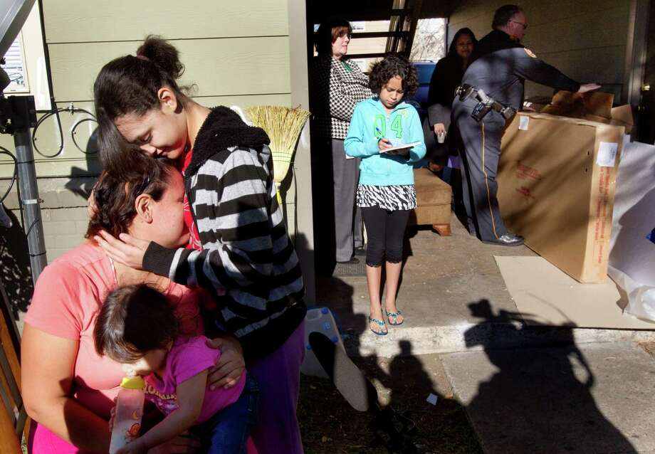 Genesis Montano embraces her mother, Patricia Mejia, as new furniture is delivered to their home by Harris County Sheriff's deputies Thursday, Dec. 13, 2012, in Houston. Photo: Brett Coomer, Houston Chronicle / © 2012 Houston Chronicle