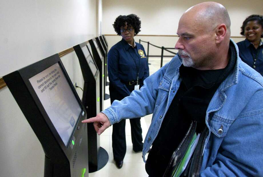 Richard Valenti uses a kiosk to check in at the Spring Driver License Mega Center grand opening Thursday, Dec. 13, 2012, in Spring. When checking in at a kiosk, customers can elect to receive a text message and updates of their wait time, or, they can receive a paper printout. The center will be staffed by 36 full-time employees and can process 700 or more customer transactions daily. Photo: Cody Duty, Houston Chronicle / © 2012 Houston Chronicle
