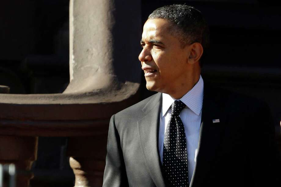 President Barack Obama walks from Blair House across Pennsylvania Avenue as he returns to the White House in Washington, Thursday, Dec. 13, 2012, after attending a holiday party for the National Security Council. (AP Photo/Charles Dharapak) Photo: Charles Dharapak