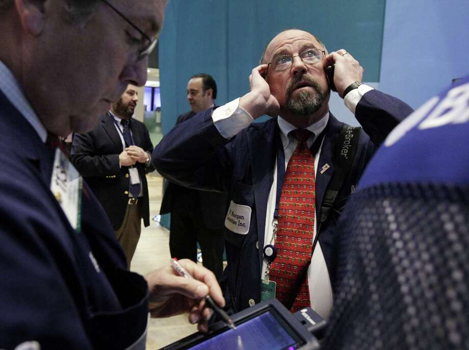 FILE - In this Tuesday, Dec. 11, 2012, file photo, Trader Frederick Reimer, right, works on the floor of the New York Stock Exchange. Stocks opened close to break-even Thursday after the government said weekly applications for unemployment benefits fell to the second-lowest level this year. (AP Photo/Richard Drew, file) Photo: Richard Drew