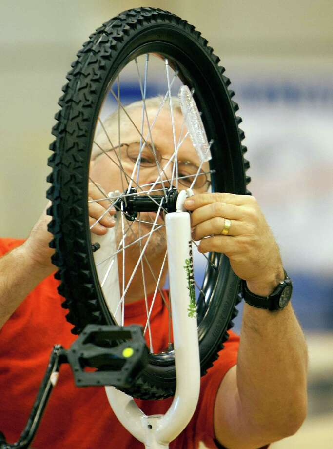 Janet Kuhlmann rolls out an assembled bike - amid the ranks of thousands - which are assembled at Reliant Arena by volunteers. Photo: Cody Duty, Staff / © 2012 Houston Chronicle