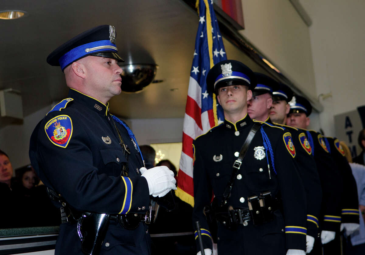 Stamford Police Honor Guard, Erin Trew, far left, stands at attention before posting the colors during the swearing in ceremony for Interim police Chief Jon Fontneau at the Stamford Government Center on Thursday, Dec. 13, 2012.