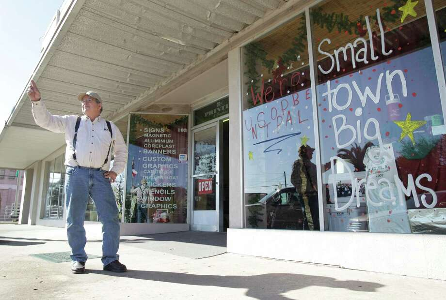 "Donnie Roddy, owner of R&R Printing & Graphics, waves to a passing motorist outside his print shop where ""Small town, Big Dreams""  is painted on the storefront window in support of the El Campo High School football team's bid for a state title Thursday, Dec. 13, 2012, in El Campo. Photo: Melissa Phillip, Houston Chronicle / © 2012 Houston Chronicle"