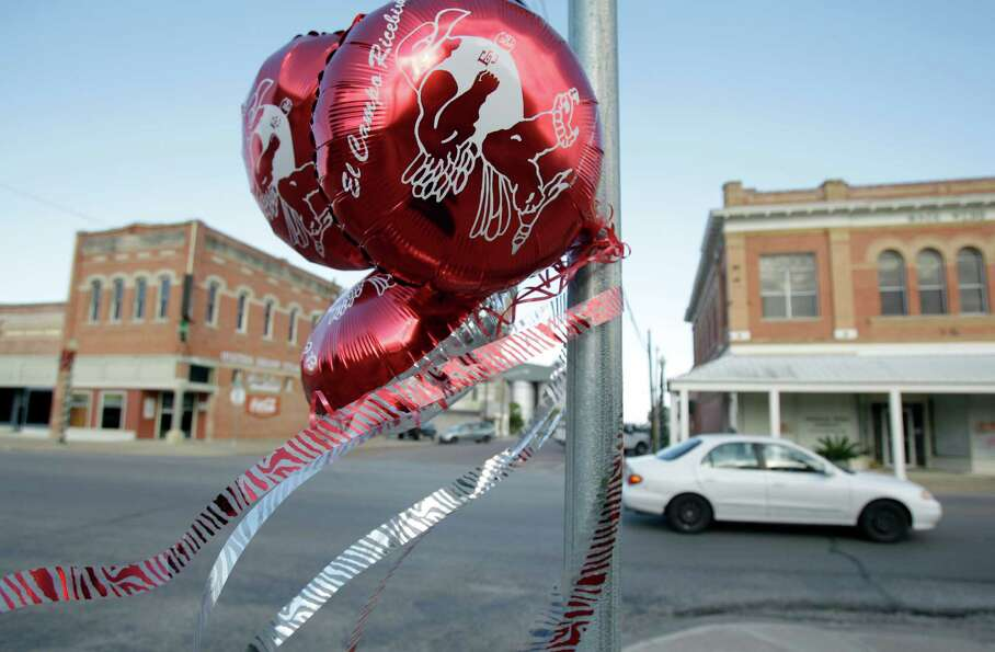 Balloons in support of the El Campo High School football team's state bid are attached to a stop sig