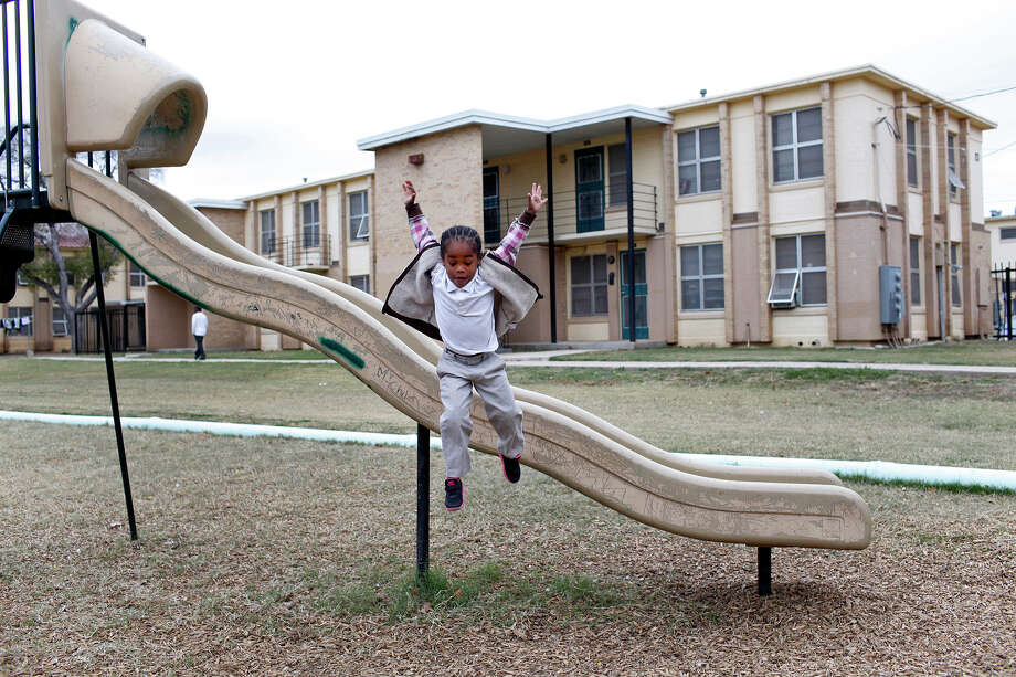 Wheatley Courts resident Shanyce Murray, 5, jumps from a slide on the playground at the apartment complex in San Antonio on Thursday, Dec. 13, 2012. The neighborhood will undergo a major renovation with the award of a $29.7 million grant from the U.S. Department of Housing and Urban Development. Murray has lived in a three bedroom apartment with her parents and four siblings at Wheatley Courts for three years. Photo: Lisa Krantz, San Antonio Express-News / © 2012 San Antonio Express-News
