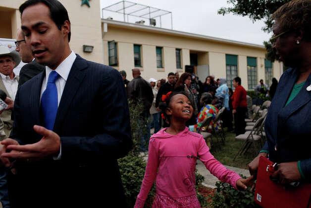 Sydney Jackson, 8, waits to meet Mayor Julian Castro, left, with her grandmother, Kathy Harris, right, President of the Skyline Park Neighborhood Association, after an event at Wheatley Courts to announce that the neighborhood will undergo a major renovation with the award of a $29.7 million grant from the U.S. Department of Housing and Urban Development. Photo: Lisa Krantz, San Antonio Express-News / © 2012 San Antonio Express-News