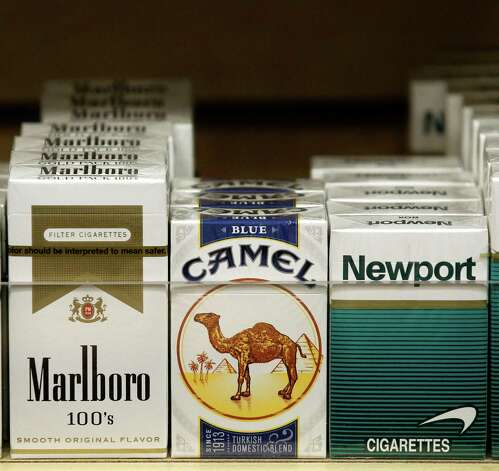 Pictured are packs of cigarettes waiting to be purchased at a Chicago area news stand Friday, Nov. 30, 2012. New tobacco products have come nearly to a halt in the U.S. because regulatory reviews for thousands of applications required by a 2009 law are taking much longer than the law requires. Though it might sound like good news from a health perspective, the halt demonstrates how tricky it is to start regulating an industry.(AP Photo/Charles Rex Arbogast) Photo: Charles Rex Arbogast