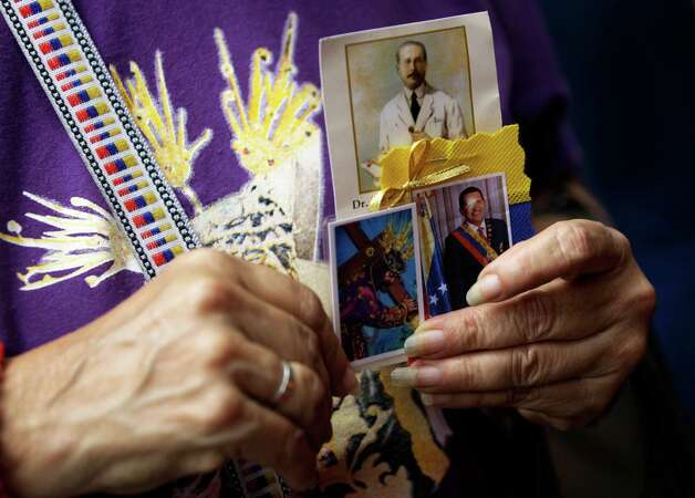 A woman holds a trio of images showing Venezuelan St. Jose Gregorio Hernandez, top, renowned as the ''Doctor of the Poor''; a laminated holy card of Jesus Christ; and an image of Venezuela's President Hugo Chavez, right, at a church service where supporters of the ailing president gathered to pray for his health, in Caracas,Venezuela, Thursday, Dec. 13, 2012.  Venezuelans were warned that Chavez may not be well enough after his fourth cancer-related surgery in Cuba to be inaugurated on Jan. 10.  (AP Photo/Fernando Llano) Photo: Fernando Llano