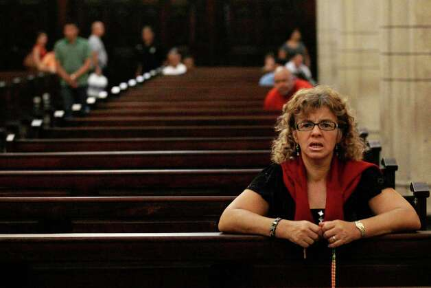 A woman recites the rosary at a local Catholic church where supporters of the ailing President Hugo Chavez gathered to pray for his health, in Caracas,Venezuela, Thursday, Dec. 13, 2012.  Venezuelans were warned that Chavez may not be well enough after his fourth cancer-related surgery in Cuba to be inaugurated on Jan. 10.  (AP Photo/Fernando Llano) Photo: Fernando Llano