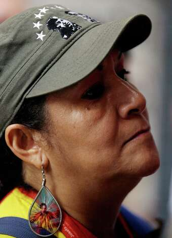 A woman donning images of  Venezuela's President Hugo Chavez attends an outdoor church service in front of the National Assembly, where supporters of  gathered to pray for his health, in Caracas,Venezuela, Thursday, Dec. 13, 2012.  Venezuelans were warned that their ailing president may not be well enough after his fourth cancer-related surgery in Cuba to be inaugurated on Jan. 10.  (AP Photo/Fernando Llano) Photo: Fernando Llano