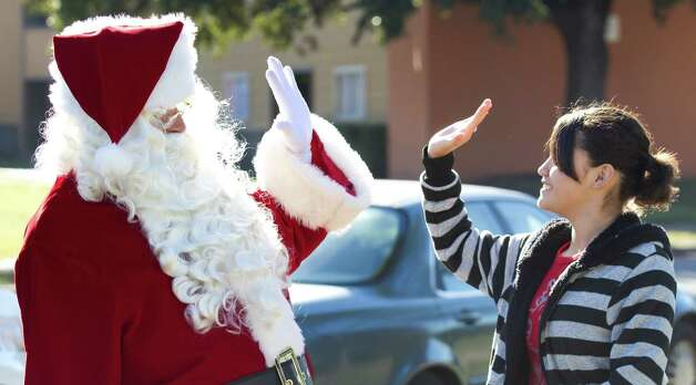 Lt. Ruben Diaz, dressed as Santa, left, high-fives Genesis Montano as new furniture is delivered to her home by Harris County Sheriff's deputies Thursday, Dec. 13, 2012, in Houston. Photo: Brett Coomer, Houston Chronicle / © 2012 Houston Chronicle