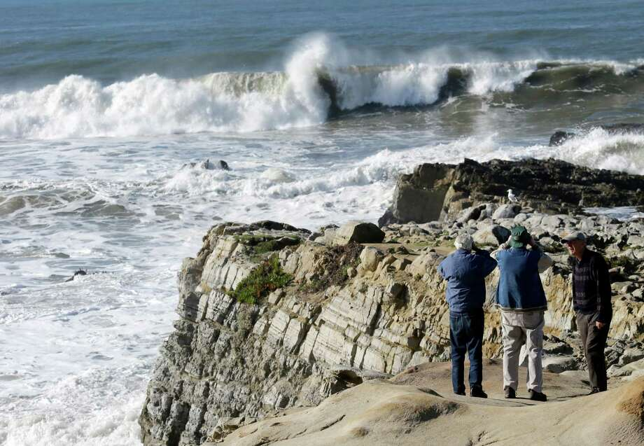 Visitors watch waves crash on a cliff in Pescadero, Calif., Thursday, Dec. 13, 2012. The National Weather Service says so-called King Tides, caused by a rather unique combination of how the sun, the moon and the earth align, will bring the highest tides of the year on Thursday, Friday and Saturday mornings. Along with the high tides, forecasters say a building swell will bring large breaking waves to area beaches. Photo: Marcio Jose Sanchez, Associated Press / AP