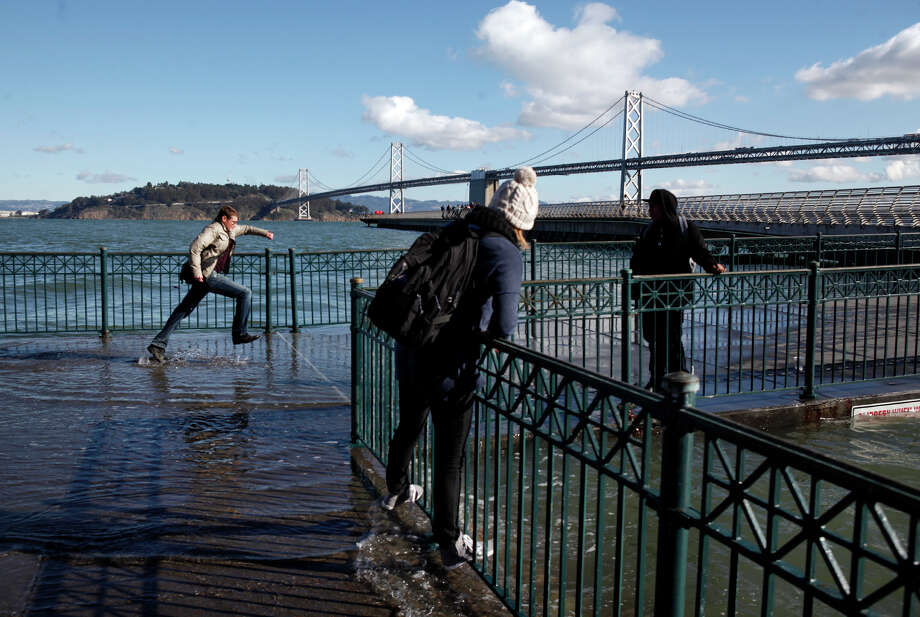 Pedestrians cannot resist getting close to Thursday's king's tide cresting along the San Francisco Embarcadero on Thursday, Dec. 13, 2012. The tide measured 7.2 at the Golden Gate and was the highest of the year. The king tides are expected to peak during the next several days, with surges over 9 feet in some areas. The phenomenon is caused by a unique alignment of the sun, moon and earth. Photo: Karl Mondon, Associated Press / San Jose Mercury News