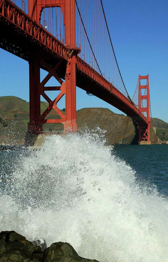 A wave breaks under the Golden Gate Bridge at high tide Thursday, Dec. 13, 2012 in San Francisco. The National Weather Service says so-called King Tides — caused by a rather unique combination of how the sun, the moon and the earth align — will bring the highest tides of the year on Thursday, Friday and Saturday mornings. Along with the high tides, forecasters say a building swell will bring large breaking waves to area beaches. The San Francisco Chronicle reports the combination of high tides and surf has flooded some parking lots in San Francisco and in Marin County. Photo: Ben Margot, Associated Press / AP